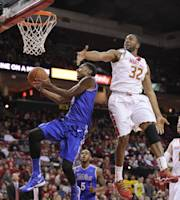 Tulsa forward Rashad Smith, left, goes to the basket against Maryland guard/forward Dez Wells (32) during the first half of an NCAA college basketball game on Sunday, Dec. 29, 2013, in College Park, Md. Tulsa guard Tim Peete (5) watches the play. (AP Photo/Nick Wass)