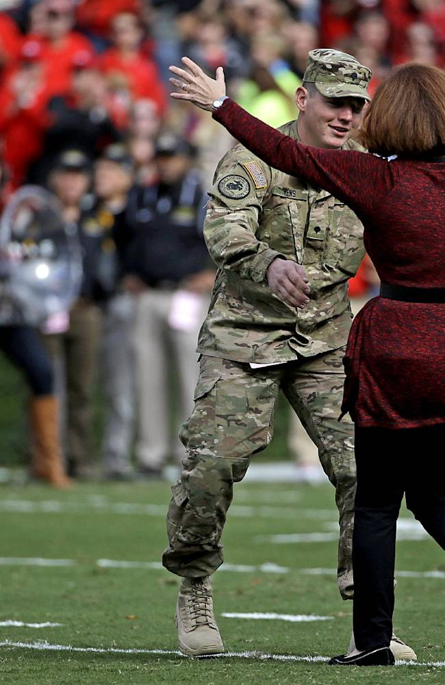 Mary Brown, right, of Athens, Ga., runs to embrace her son, Georgia National Guard Spc. Robert Owens, 23, left, as he surprises her on the field while returning from his deployment in Afghanistan three weeks early during the first half of an NCAA college football game between Georgia and Appalachian State, Saturday, Nov. 9, 2013, in Athens, Ga