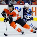Philadelphia Flyers' Michael Del Zotto (15), left, takes the puck as Winnipeg Jets' Andrew Ladd (16), right, follows in the first period of an NHL hockey game, Thursday, Jan. 29, 2015, in Philadelphia. (AP Photo/Tom Mihalek)