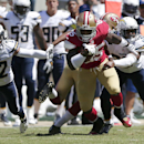 San Francisco 49ers tight end Vernon Davis (85) runs against San Diego Chargers cornerback Jason Verrett (22) and strong safety Marcus Gilchrist (38) during the second quarter of an NFL preseason football game in Santa Clara, Calif., Sunday, Aug. 24, 2014