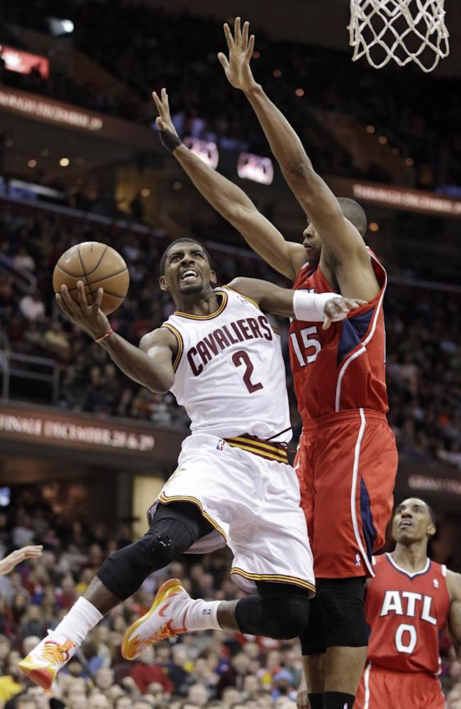 Cleveland Cavaliers' Kyrie Irving (2) jumps to the basket against Atlanta Hawks' Al Horford (15 during the fourth quarter of an NBA basketball game Thursday, Dec. 26, 2013, in Cleveland