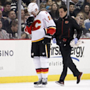 Calgary Flames' Ladislav Smid (15) is followed by a trainer as he skates off the ice after taking a hit from Pittsburgh Penguins' Simon Despres during the second period of an NHL hockey game in Pittsburgh Friday, Dec. 12, 2014. Smid did not return to the