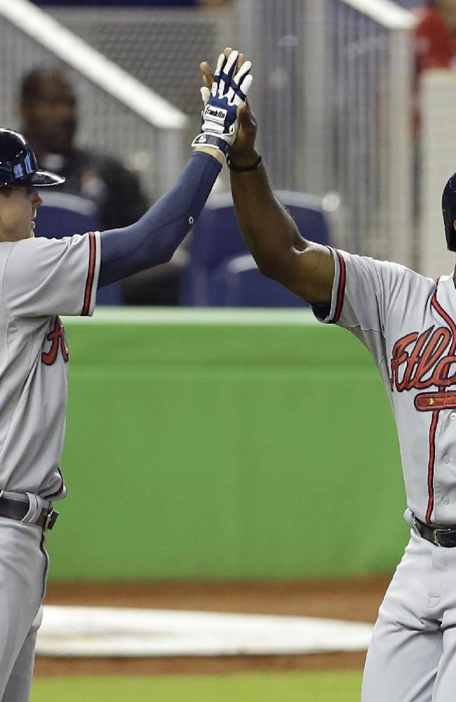 Atlanta Braves' Elliot Johnson (30) and Justin Upton, right, high five after scoring on a double hit by Evan Gattis in the third inning during a baseball game against the Miami Marlins, Thursday, Sept. 12, 2013, in Miami