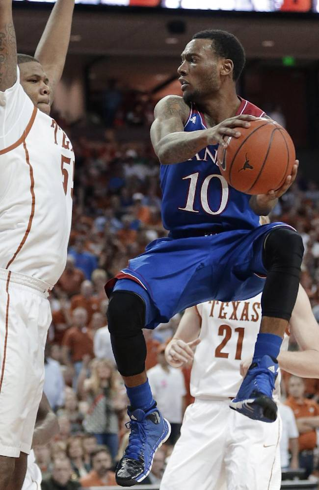 Kansas' Naadir Tharpe (10) looks to pass around Texas' Cameron Ridley (55) during the second half of an NCAA college basketball game, Saturday, Feb. 1, 2014, in Austin, Texas. Texas won 81-69