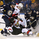 Ottawa Senators right wing Mark Stone loses his footing as he battles for the puck between St. Louis Blues defensemen Carl Gunnarsson, left, and Kevin Shattenkirk, right, during the third period of an NHL hockey game, Tuesday, Nov. 25, 2014, at the Scottr