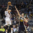 Milwaukee Bucks' Ersan Ilyasova, left, shoots a three pointer over Utah Jazz Gordon Hayward during the second half of an NBA basketball game Monday, March 3, 2014, in Milwaukee The Associated Press