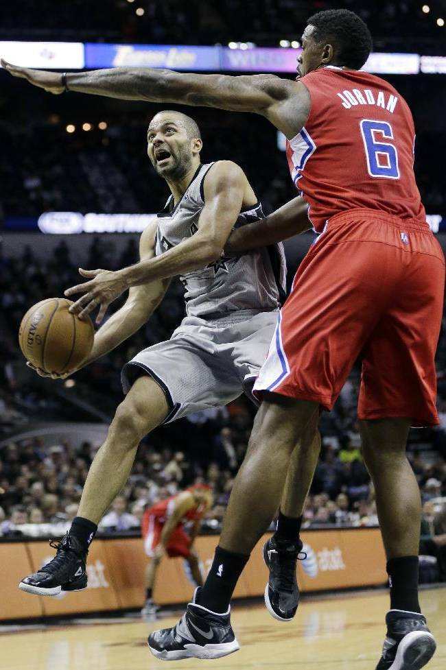 San Antonio Spurs' Tony Parker (9), of France, drives around Los Angeles Clippers' DeAndre Jordan (6) during the first half on an NBA basketball game, Saturday, Jan. 4, 2014, in San Antonio