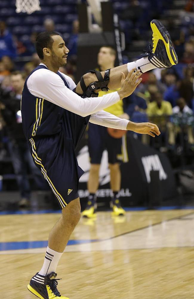 Michigan's Jon Horford stretches during practice for their NCAA Midwest Regional semifinal college basketball tournament game Thursday, March 27, 2014, in Indianapolis. Michigan plays Tennessee on Friday, March 28, 2013
