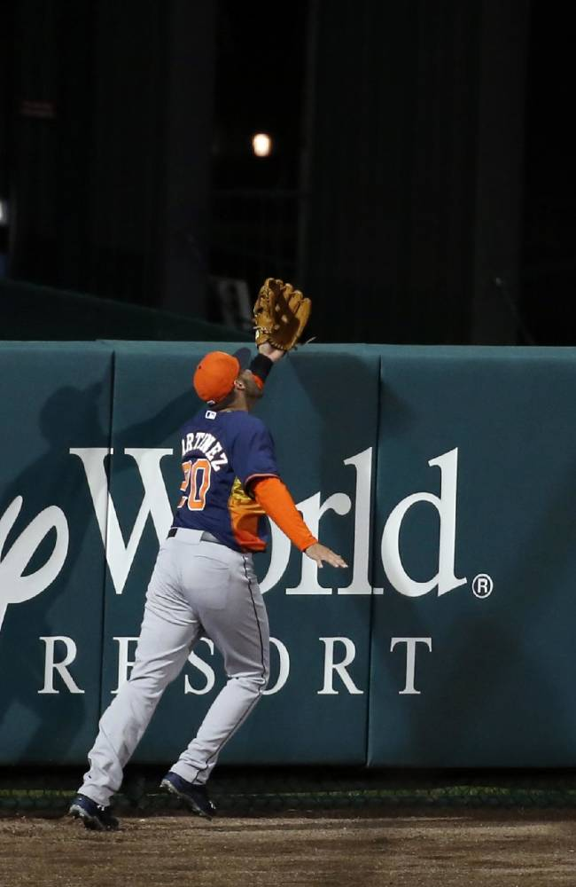 Houston Astros left fielder J.D. Martinez can't catch a solo home run by Atlanta Braves' Todd Cunningham, in the eighth inning of an exhibition baseball game, Friday, Feb. 28, 2014, in Kissimmee, Fla. The Astros won 7-5