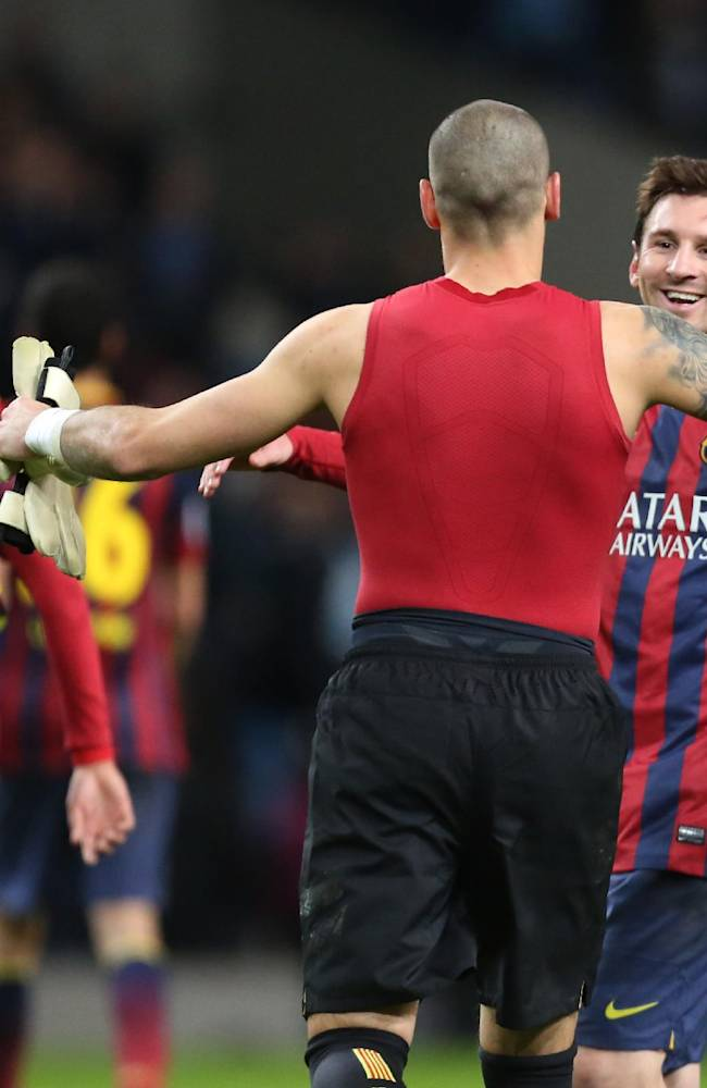Barcelona goalkeeper Victor Valdes celebrates with Barcelona's Lionel Messi at the end of the Champions League first knock out round soccer match between Barcelona and Manchester City at the Etihad Stadium, Manchester, England, Tuesday Feb. 18, 2014