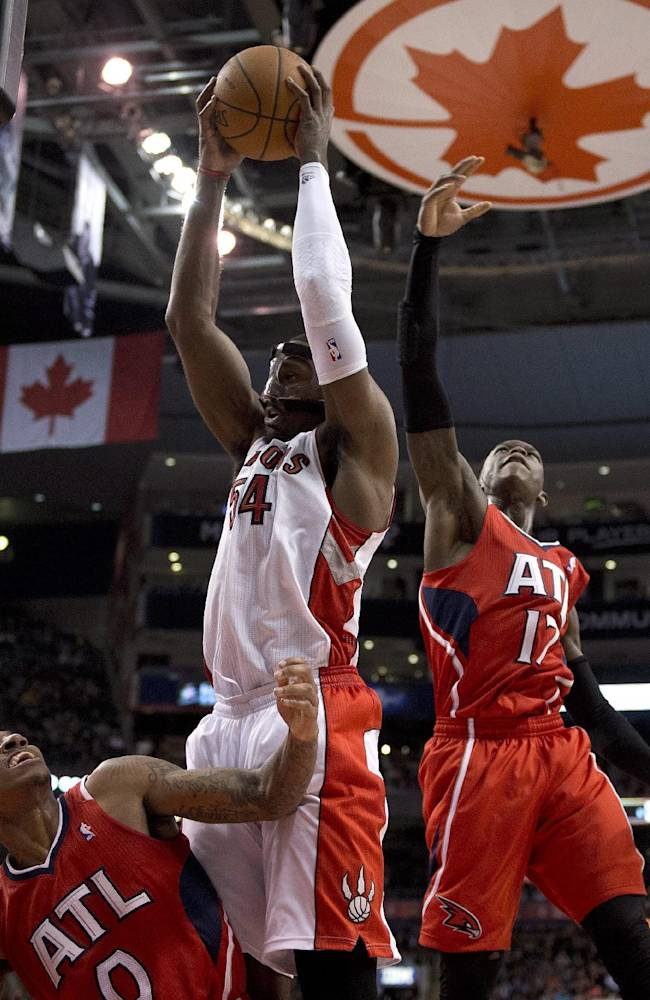 Toronto Raptors forward Patrick Patterson (54) rebounds against Atlanta Hawks guards Jeff Teague (0) and Dennis Schroder (17) during fourth-quarter NBA basketball game action in Toronto, Wednesday, Feb. 12, 2014