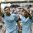 Manchester City's Frank Lampard, left, celebrates with Pablo Zabaleta after scoring his side's fourth goal against Hull City in their English Premier League match at the KC Stadium, Hull England Saturday Sept. 27, 2014.