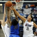 Connecticut's Breanna Stewart, left blocks a shot attempt by DePaul's Jasmine Penny, center, as Connecticut's Stefanie Dolson, right, defends during the first half of an NCAA college basketball game in Storrs, Conn., Sunday, Feb. 10, 2013. (AP Photo/Jessica Hill)