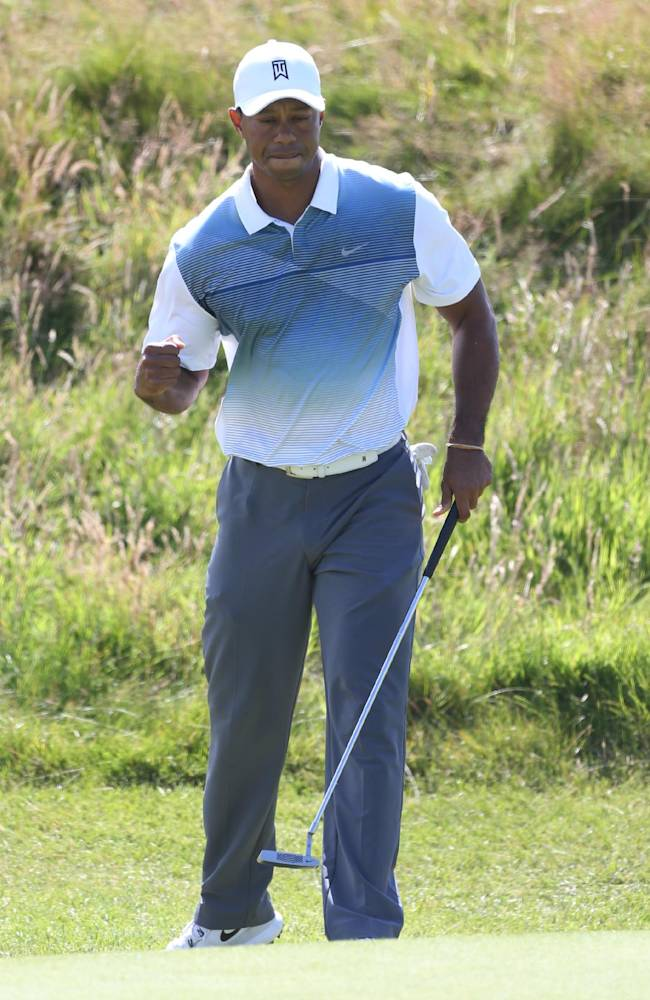 Tiger Woods of the US celebrates after a birdie on the 11th hole during the first day of the British Open Golf championship at the Royal Liverpool golf club, Hoylake, England, Thursday July 17, 2014