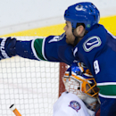 Vancouver Canucks' Zack Kassian, right, is checked into New York Islanders goalie Jaroslav Halak, of Slovakia, by Nick Leddy during the third period of an NHL hockey game Tuesday, Jan. 6, 2015, in Vancouver, British Columbia The Associated Press