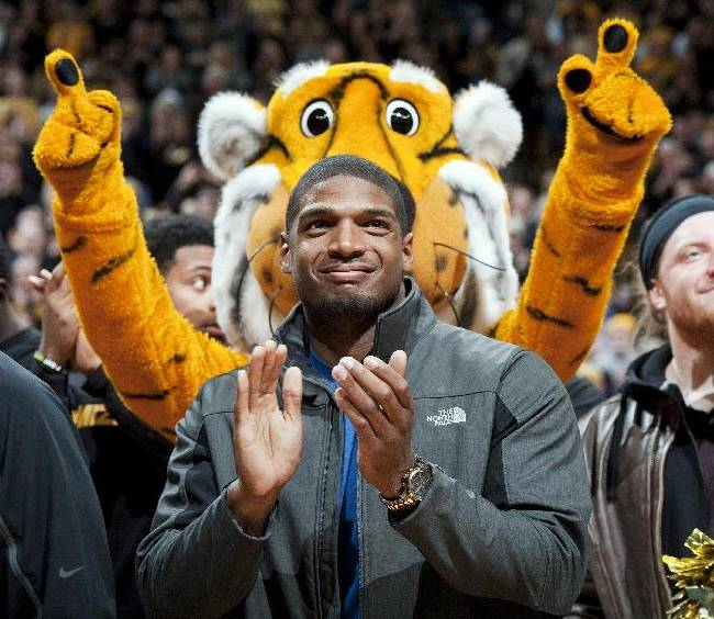 In this Feb. 15, 2014, file photo, Missouri's All-American defensive end Michael Sam claps during the Cotton Bowl trophy presentation at halftime of an NCAA college basketball game between Missouri and Tennessee in Columbia, Mo. The NFL draft will conclude with Rounds 4 through 7 on Saturday, and when and if Sam is selected is sure to be the most significant development. The Southeastern Conference defensive player of the year last season for Missouri came out as gay in media interviews this year