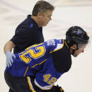 St. Louis Blues' David Backes (42) is helped off the ice by a Blues trainer against the Chicago Blackhawks during the third period in Game 2 of a first-round NHL hockey playoff series, Saturday, April 19, 2014, in St. Louis. (AP Photo/Bill Boyce)