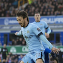 Manchester City's David Silva, top, is tackled by Everton's Muhamed Besic during the English Premier League soccer match between Everton and Manchester City at Goodison Park Stadium, Liverpool, England, Saturday Jan. 10, 2015