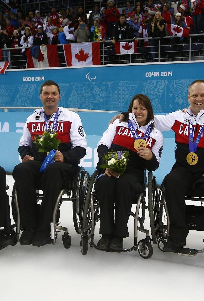 From left, Canada's Jim Armstrong, Mark Ideson, Ina Forrest, Dennis Thiessen, and Sonja Gaudet pose after winning gold medals at the wheelchair curling match between Russia and Canada at the 2014 Winter Paralympics in Sochi, Russia, Saturday, March 15, 2014. Canada won 8-3