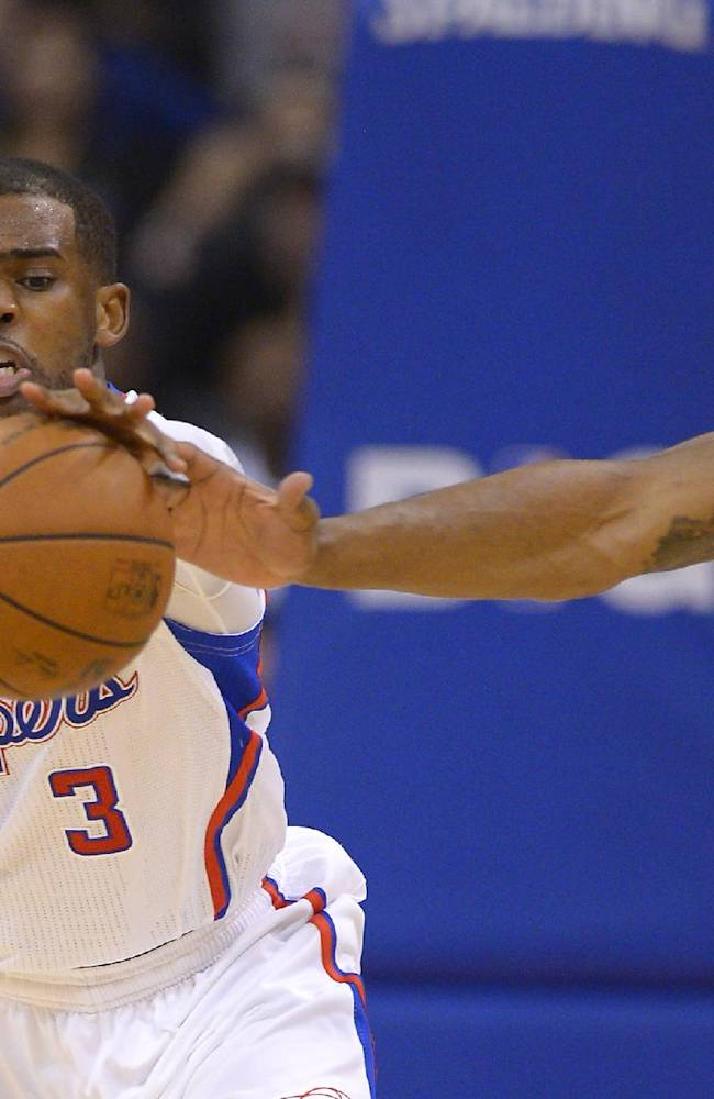 Los Angeles Clippers guard Chris Paul, left, reaches for a loose ball along with Houston Rockets forward Terrence Jones during the first half of an NBA basketball game, Wednesday, Feb. 26, 2014, in Los Angeles