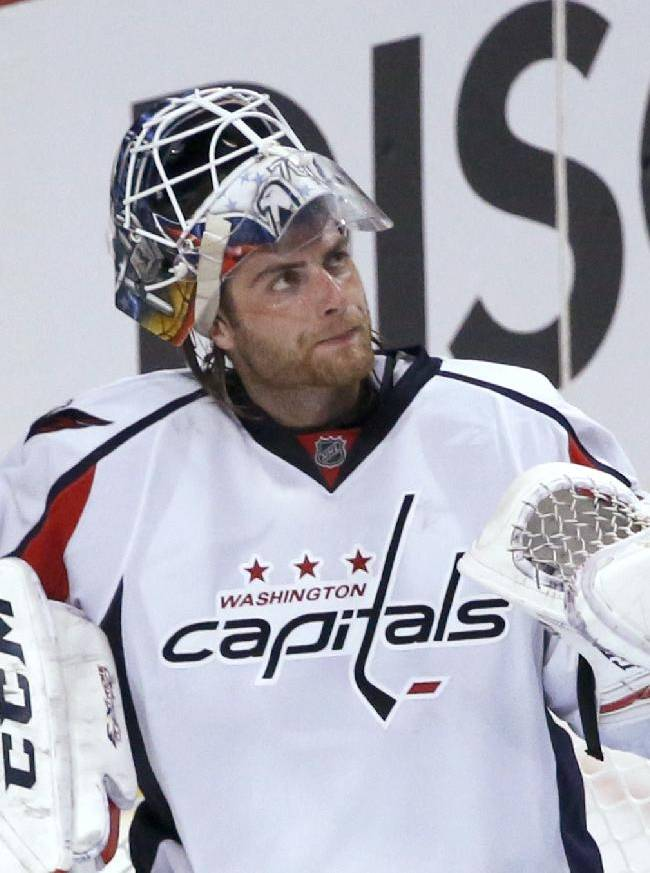 Washington Capitals goalie Braden Holtby looks up at the scoreboard during the third period of an NHL hockey game against the Chicago Blackhawks on Tuesday, Oct. 1, 2013, in Chicago. The Blackhawks won 6-4