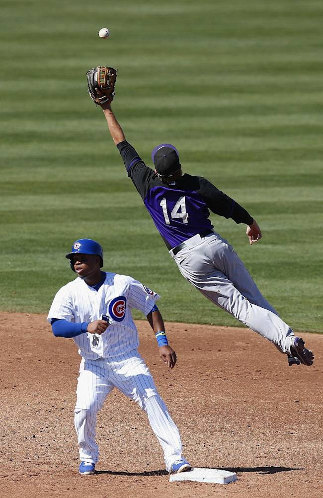 Colorado Rockies' Josh Rutledge (14) jumps to get a relay throw as Chicago Cubs' Luis Valbuena, left, stands on second base during the third inning of an exhibition spring baseball game Tuesday, March 11, 2014, in Mesa, Ariz. The Rockies defeated the Cubs 13-0