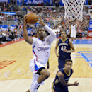 Los Angeles Clippers guard Chris Paul, left, goes up for a shot as New Orleans Pelicans guard Brian Roberts, lower right, defends while center Alexis Ajinca, of France, looks on during the first half of an NBA basketball game, Saturday, March 1, 2014, in
