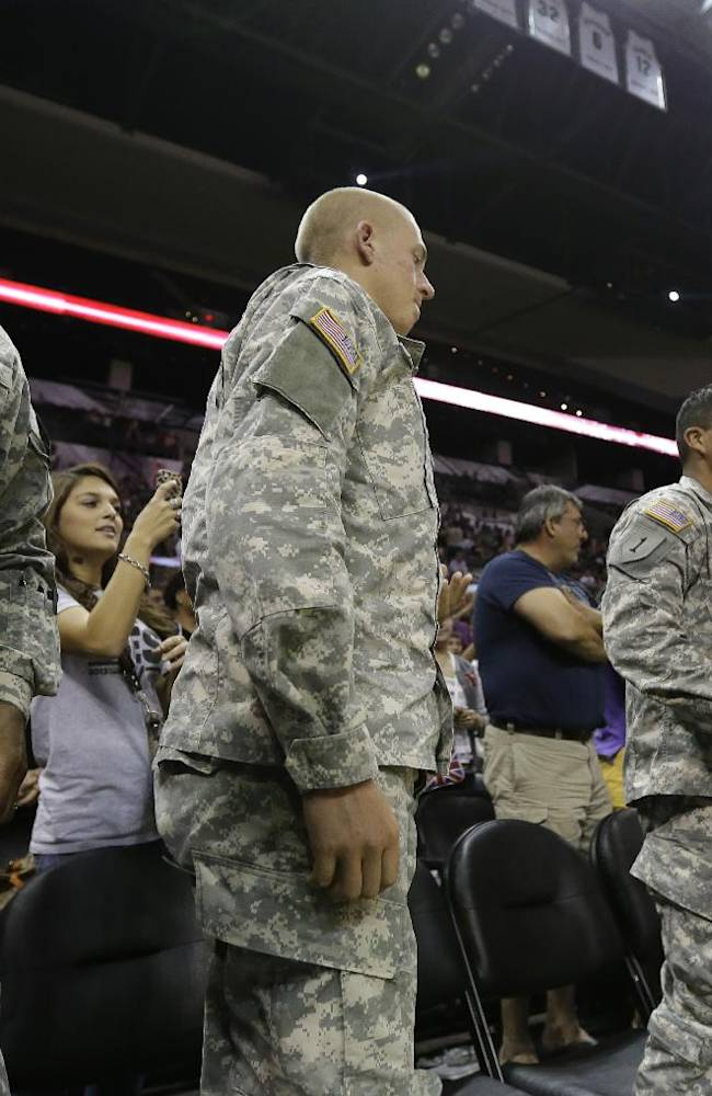 San Antonio Spurs head coach Gregg Popovich, right, greets members of the military following an open NBA basketball practice, Sunday, Oct. 6, 2013, in San Antonio