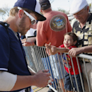 Milwaukee Brewers' Mark Reynolds, left, signs an autograph John Anthony Santiago, 4, as his grandfather Anthony Santiago, right, helps him up to get closer to Reynolds during spring training baseball practice, Wednesday, Feb. 26, 2014, in Phoenix The Asso