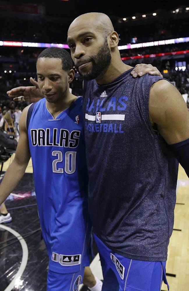 Dallas Mavericks' Devin Harris (20) and Vince Carter (25) walk off the court arm-in-arm after their loss to San Antonio Spurs in Game 7 of the opening-round NBA basketball playoff series, Sunday, May 4, 2014, in San Antonio. San Antonio won 119-96