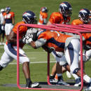 Denver Broncos' Winston Justice, left foreground, and Ryan Clady, right foreground, run a drill during NFL football training camp on Monday, July 28, 2014, in Englewood, Colo. (AP Photo/Jack Dempsey)