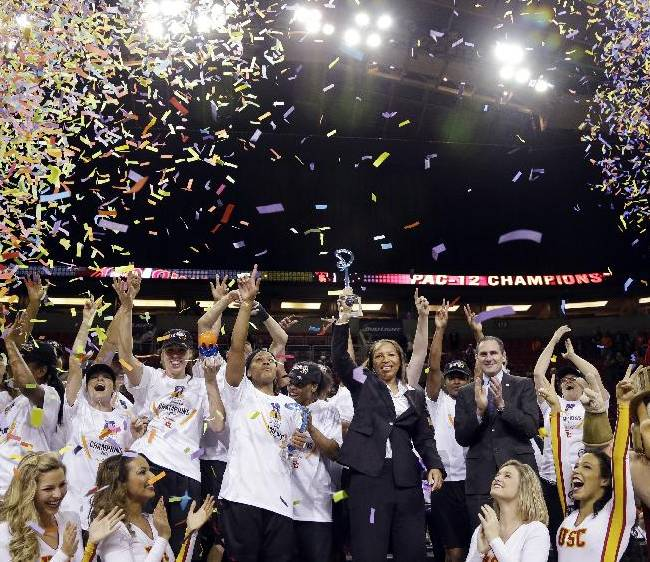 Southern California head coach Cynthia Cooper, center, holds the trophy as she stands with her team on an award podium after they beat Oregon State to win the Pac-12 NCAA college championship basketball game Sunday, March 9, 2014, in Seattle.  USC won 71-62