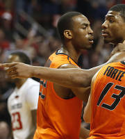 Oklahoma State's Marcus Smart is held back by teammates after he pushed a fan in the stands. (AP)
