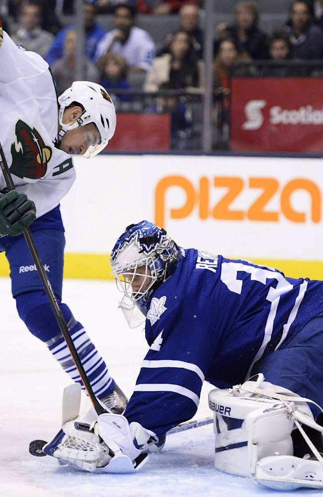 Toronto Maple Leafs goaltender James Reimer battles tries to keep the puck from Minnesota Wild's Zach Parise during the first period of an NHL hockey game in Toronto on Tuesday, Oct. 15, 2013