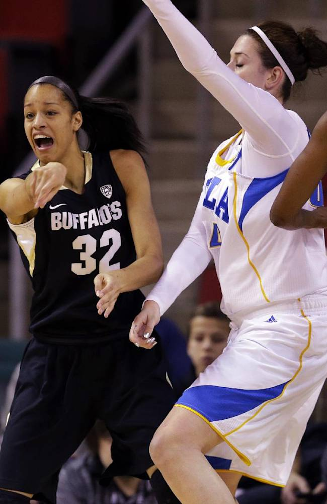 Colorado forward Arielle Roberson (32) passes around the defense of UCLA's Luiana Livulo (13) and Corinne Costa, second from right, in the first half of an NCAA college basketball game in the Pac-12 women's tournament, Thursday, March 6, 2014, in Seattle
