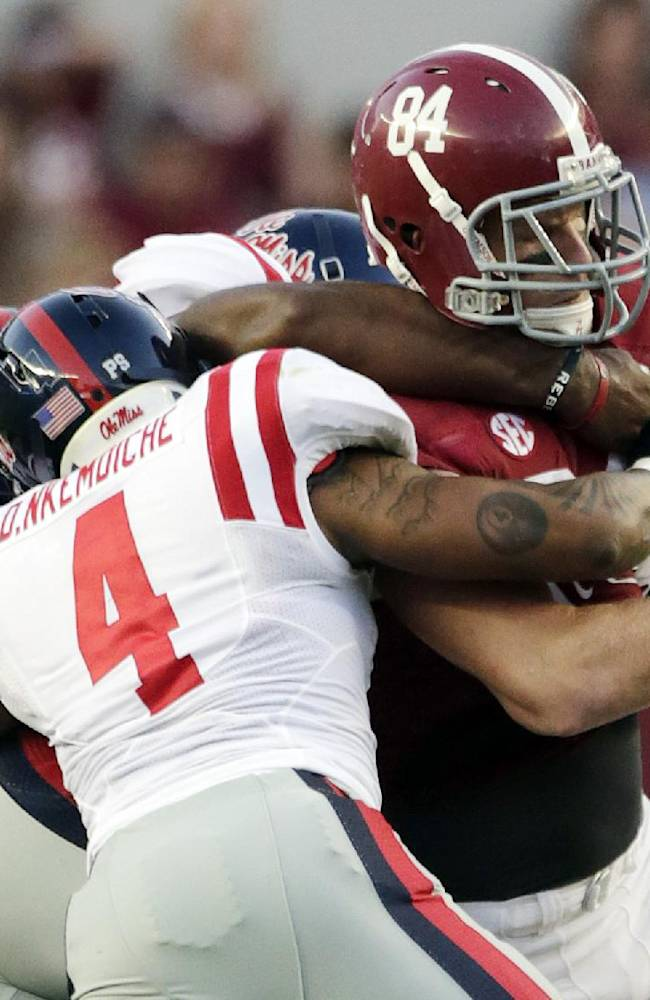 Alabama tight end Brian Vogler (84) fumbles as he is taken down by Mississippi linebacker Denzel Nkemdiche (4) and two other Mississippi players during the first half of an NCAA college football game in Tuscaloosa, Ala., Saturday, Sept. 28, 2013. Alabama recovered the fumble