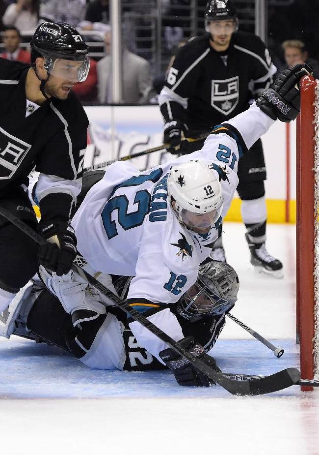 San Jose Sharks center Patrick Marleau, center, falls over Los Angeles Kings goalie Jonathan Quick, lower right, as defensemen Alec Martinez, left, and Slava Voynov, of Russia, watch during the third period in Game 6 of an NHL hockey first-round playoff series, Monday, April 28, 2014, in Los Angeles. The Kings won 4-1. (AP Photo)