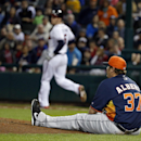Houston Astros relief pitcher Matt Albers sits on the ground as Atlanta Braves' Freddie Freeman runs to first in the fourth inning of a spring training baseball game, Friday, Feb. 28, 2014, in Kissimmee, Fla. Freeman hit the ball back to Albers who was no
