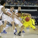 Michigan's Trey Burke (3) drives against Florida's Mike Rosario (3), Erik Murphy, second from left, and Scottie Wilbekin during the first half of a regional final game in the NCAA college basketball tournament, Sunday, March 31, 2013, in Arlington, Texas. (AP Photo/Tony Gutierrez)