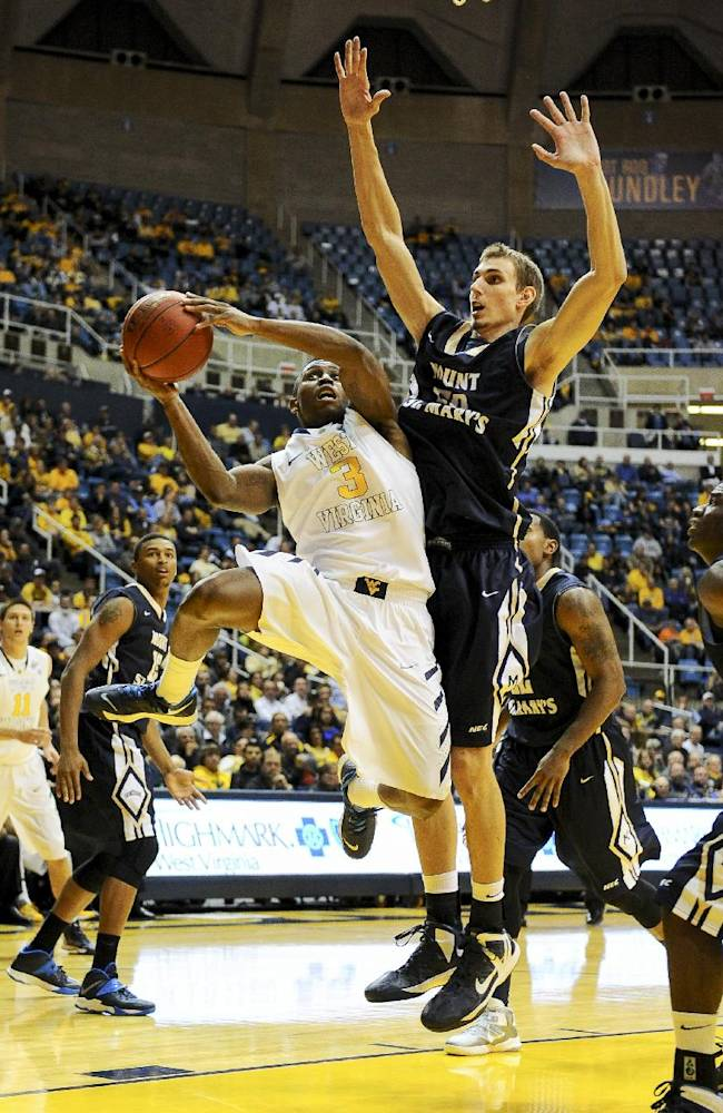 West Virginia's Juwan Staten (3) drives the lane against Mount St. Mary's Taylor Danaher (50) during the second half of an NCAA college basketball game in Morgantown, W.Va., Friday, Nov. 8, 2013. West Virginia won 77-62