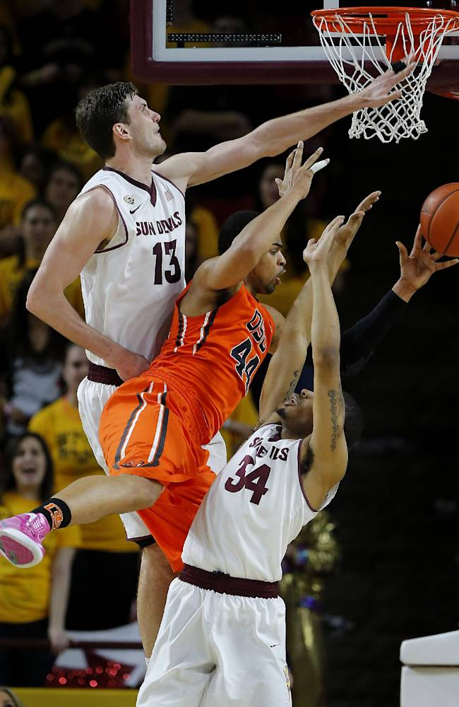 Oregon State's Devon Collier, center, passes around Arizona State's Jordan Bachynski (13) and Jermaine Marshall during the second half of an NCAA college basketball game, Thursday, Feb. 6, 2014, in Tempe, Ariz