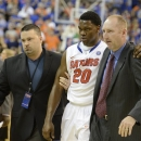 Florida team doctor Kevin Farmer, left, and athletic trainer Dave Werner, right, help Florida guard Michael Frazier II (20) from the floor after he was injured against Arkansas in the second half of an NCAA college basketball game in Gainesville, Fla., Saturday, Feb. 23, 2013. Florida won 71-54. (AP Photo/Phil Sandlin)