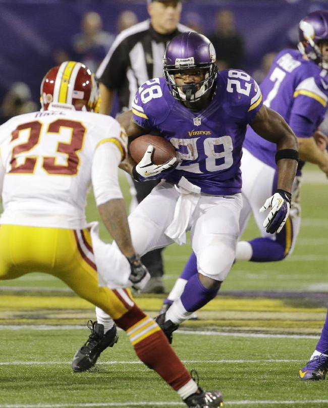 Minnesota Vikings running back Adrian Peterson (28) looks to get past Washington Redskins cornerback DeAngelo Hall (23) during the second half of an NFL football game, Thursday, Nov. 7, 2013, in Minneapolis