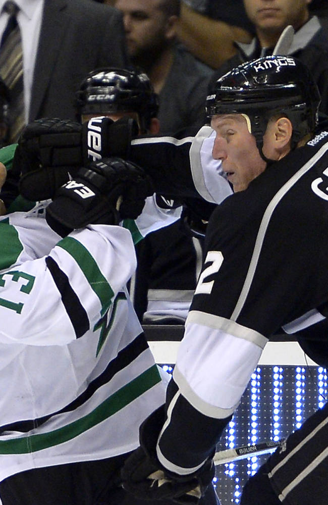 Los Angeles Kings defenseman Matt Greene, right, stiff-arms Dallas Stars left wing Ray Whitney during the third period of their NHL hockey game, Saturday, Oct. 19, 2013, in Los Angeles. The Kings won 5-2
