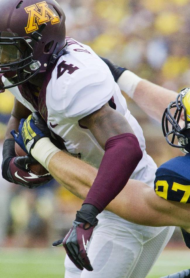 Minnesota wide receiver Donovahn Jones (4) tries to break a tackle from Michigan linebacker Brennen Beyer (97) in the first quarter of an NCAA college football game, Saturday, Oct. 5, 2013, in Ann Arbor, Mich