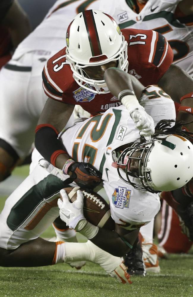 Louisville linebacker James Burgess (13) stops Miami running back Dallas Crawford (25) for a 5-yard loss during the first half of the Russell Athletic Bowl NCAA college football game in Orlando, Fla., Saturday, Dec. 28, 2013
