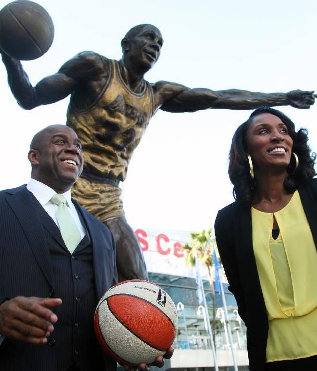 Former Los Angeles Laker Magic Johnson is joined by former Los Angeles Sparks' Lisa Leslie under a statue of Johnson after a news conference at Staples Center in Los Angeles on Wednesday, Feb 5, 2014. Johnson is part of a group buying the Sparks of the WNBA
