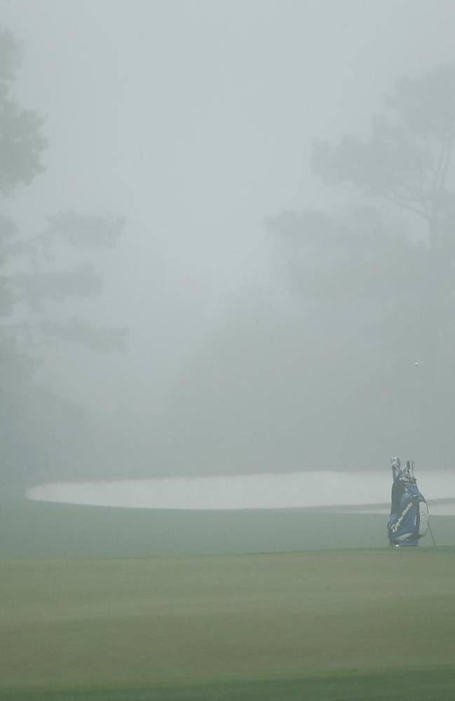 Darren Clarke, of Northern Ireland, chips onto the green in the morning mist in preparation for the Masters golf tournament Monday, April 7, 2014, in Augusta, Ga