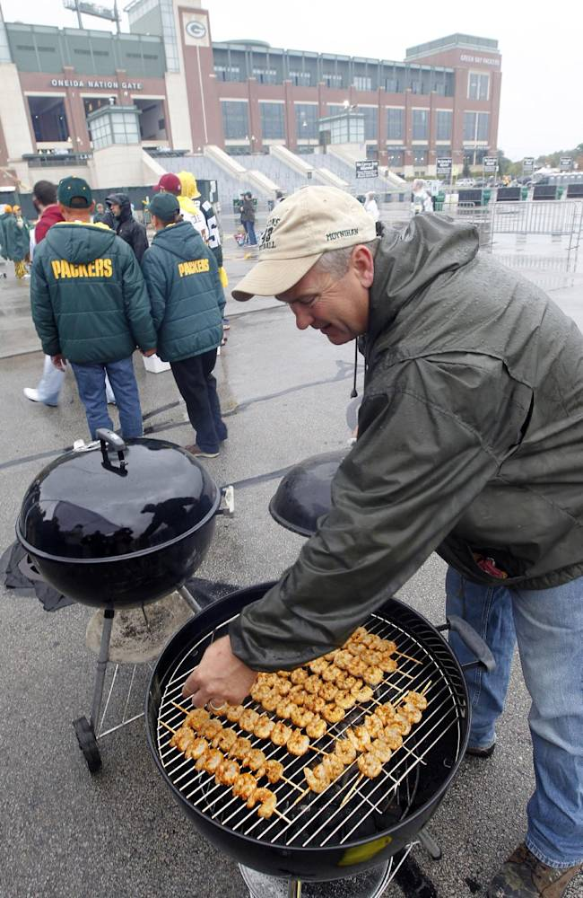 Rick Moynihan grills some shrimp in the parking lot of Lambeau Field before an NFL football game between the Green Bay Packers and the Washington Redskins Sunday, Sept. 15, 2013, in Green Bay, Wis