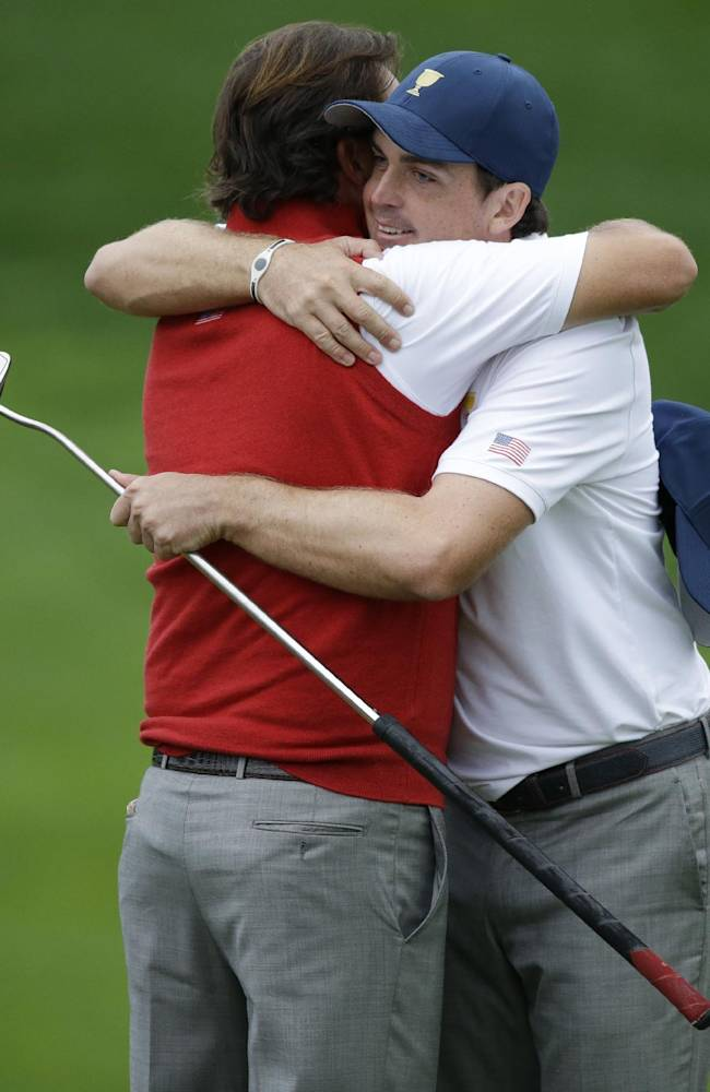 United States team player Keegan Bradley, right, is hugged by Phil Mickelson after Bradley made a birdie putt on the 18th hole during the foursome match at the Presidents Cup golf tournament at Muirfield Village Golf Club Sunday, Oct. 6, 2013, in Dublin, Ohio. Bradley and Phil Mickelson halved the match against International team player Jason Day, of Australia, and Graham DeLaet, of Canada